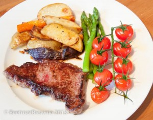 Steak with potato and carrot wedges, steamed asparagus and roasted cherry tomatoes